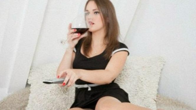 Wanita minum dan menonton televisi.