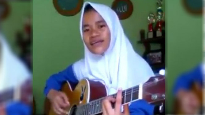 Wanita bernyanyi sambil bermain gitar.