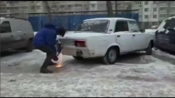 Pria gergaji bagian belakang mobil.