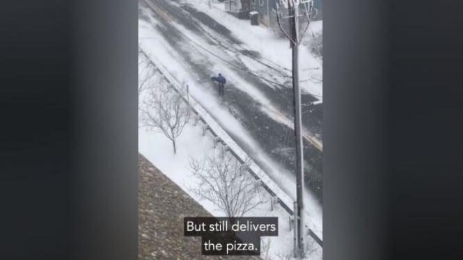 Pria mengantar pizza di tengah badai salju.