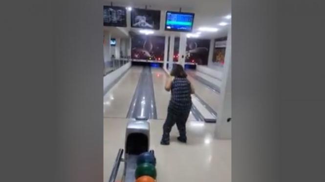 Wanita bermain boling.