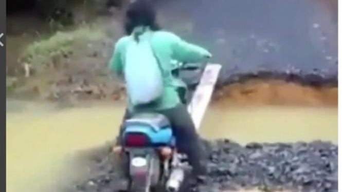 Pengendara motor lewati jembatan.