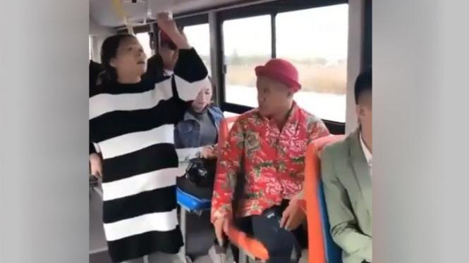 Wanita hamil berdiri di bus.