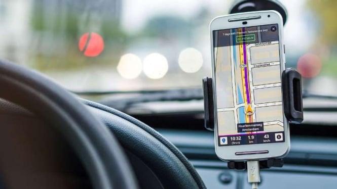 Ilustrasi mengemudi sembari mengoperasikan GPS