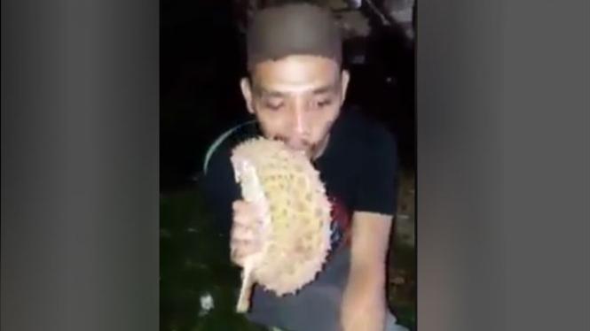 Aksi pria memakan kulit durian.