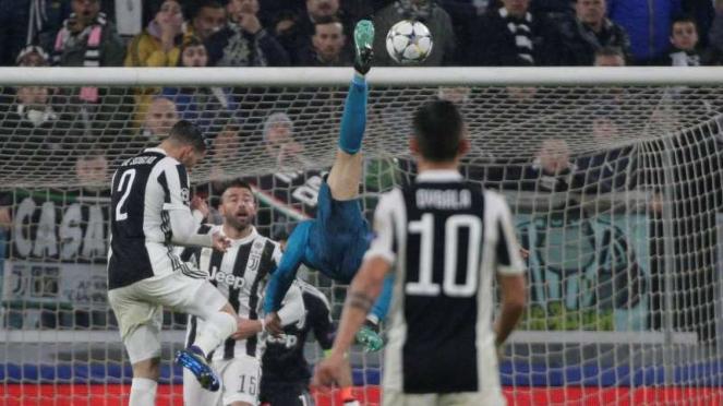 Megabintang Real Madrid, Cristiano Ronaldo (biru), melakukan tendangan salto untuk mencetak gol kedua.
