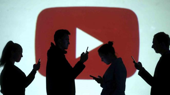 Siluet pengguna perangkat di antara logo YouTube.