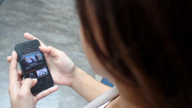 Pengguna ponsel pintar atau smartphone sedang menonton streaming video.
