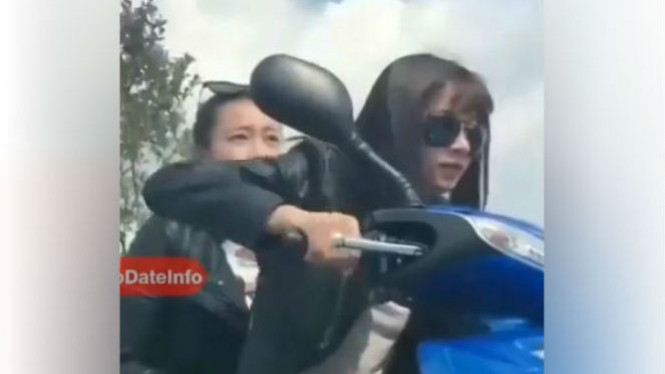 Wanita cantik berboncengan sepeda motor.