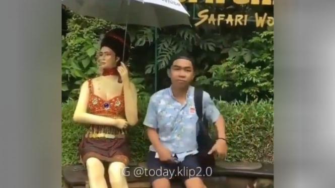 Pria berfoto dengan patung.