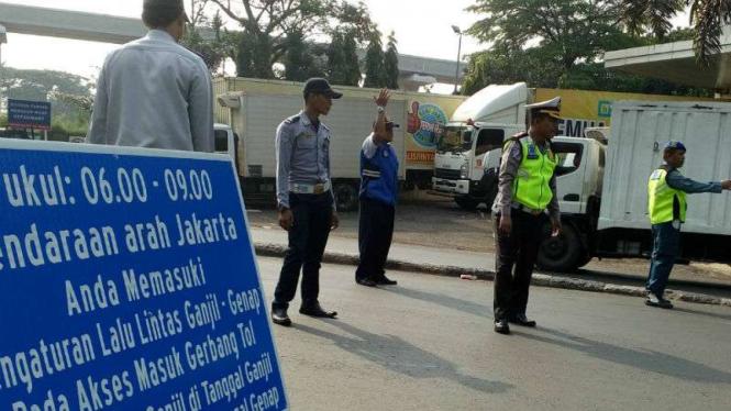 Petugas mengawasi penerapan sistem ganjil genap di depan gerbang Tol Cibubur II