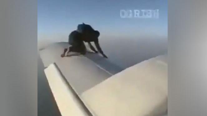 Pria merayap di sayap pesawat.