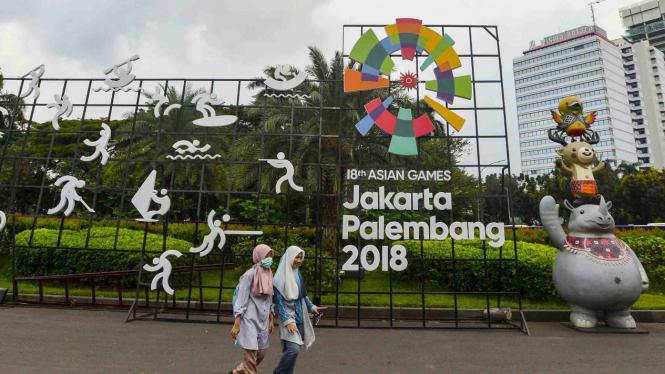 Warga berjalan di samping display promosi Asian Games 2018 di Jakarta.