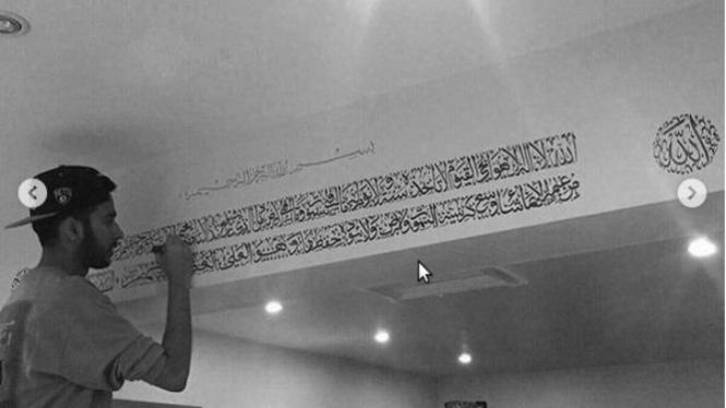 Menulis kaligrafi.