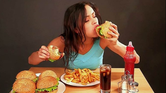 Ilustrasi makan makanan junk food.