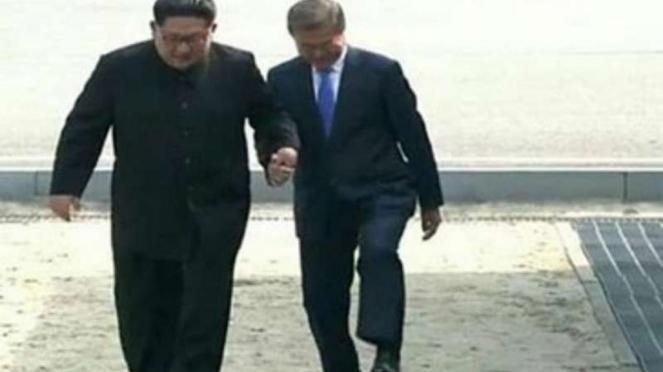 Pemimpin Korea Utara Kim Jong Un dan Presiden Korea Selatan Moon Jae In melangkah ke wilayah Korsel.