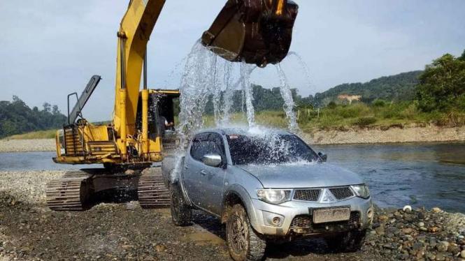 Mobil kabin ganda diguyur air dari ekskavator