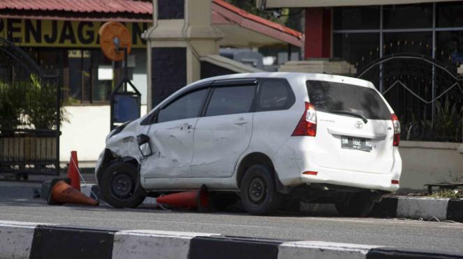Mobil minibus yang digunakan pelaku teror dalam kondisi rusak di depan pintu masuk Polda Riau