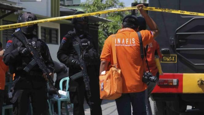 Personel Brimob bersiaga saat dilakukannya penggeledahan oleh Tim Densus 88 di kediaman terduga pelaku bom bunuh diri Polrestabes Surabaya