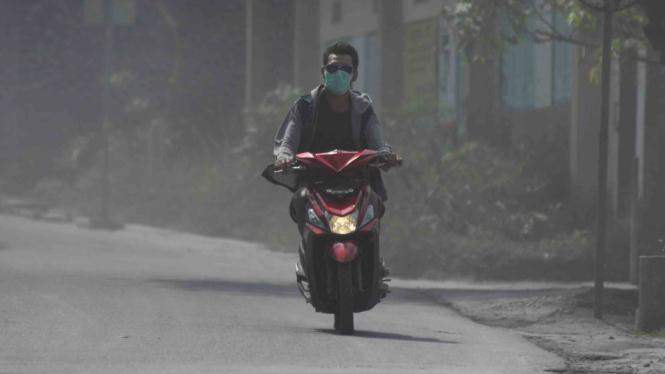 Pengendara sepeda motor mengenakan masker.