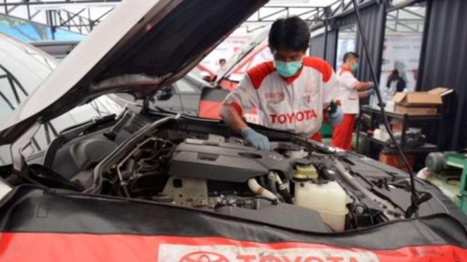 Teknisi sedang melakukan servis mobil Toyota