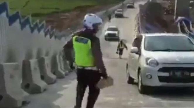 Polisi berusaha membantu mobil yang mundur lagi di tanjakan Tol Salatiga.