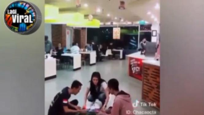Wanita dan temannya makan di lantai di sebuah restoran cepat saji.