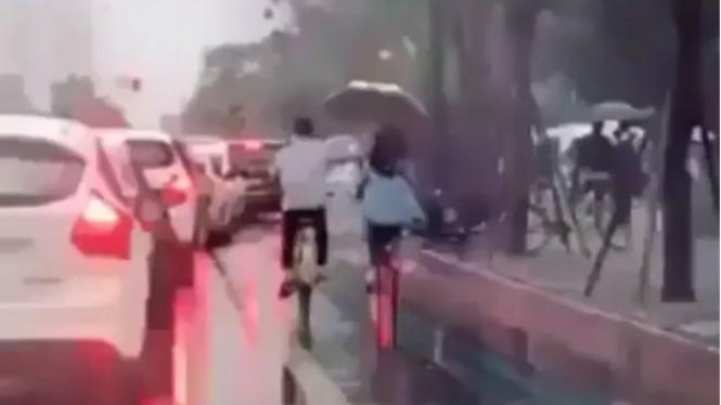 Pasangan bersepeda saat hujan.