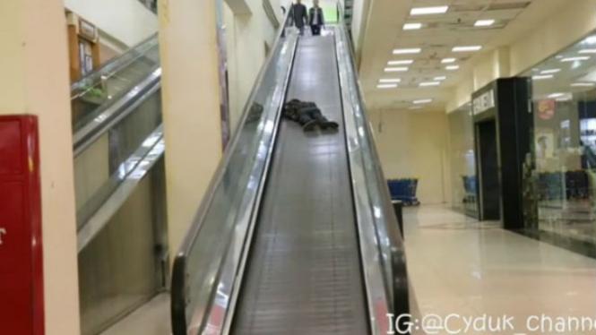 Pria tidur di eskalator.