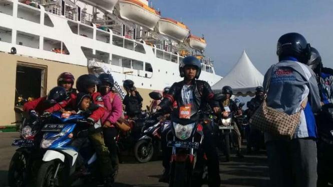 Para pemudik dengan sepeda motor saat turun dari kapal.
