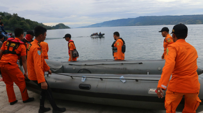 Personel Basarnas mengangkat perahu karet saat akan melakukan pencarian korban KM Sinar Bangun yang tenggelam di Danau Toba, Simalungun, Sumatera Utara, Rabu (20/6/2018).