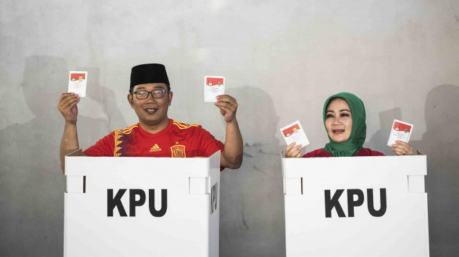 Calon Gubernur Jawa Barat nomor urut satu Ridwan Kamil (kiri) bersama istri Atalia Praratya (kanan) menunjukkan surat suara saat menggunakan hak pilih di Pilgub Jabar