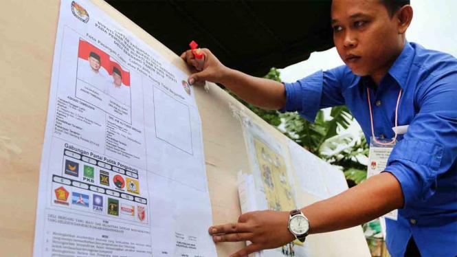 Ilustrasi Petugas KPPS merapikan poster Pilkada Serentak di Deli Serdang