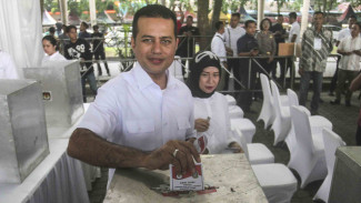 Calon Wakil Gubernur Sumut nomor urut satu Musa Rajeckshah bersama istri Sri Ayu Mihari memasukkan surat suara ke dalam kotak suara saat memberikan hak suara pada Pilkada Sumut 2018