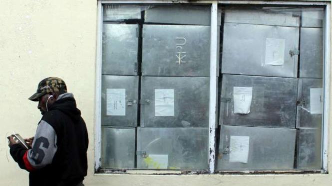 Warga berdiri di dekat tumpukan kotak suara Pilkada Mimika di kantor KPU Mimika