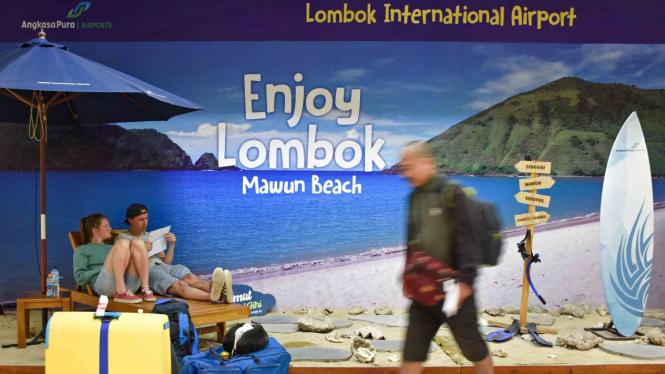 Dua wisatawan manca negara yang penerbangannya dibatalkan duduk santai di