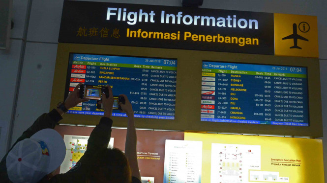 Sejumlah penumpang mencari informasi jadwal penerbangan melalui layar monitor di Bandara Ngurah Rai, Bali, Jumat, 29 Juni 2018