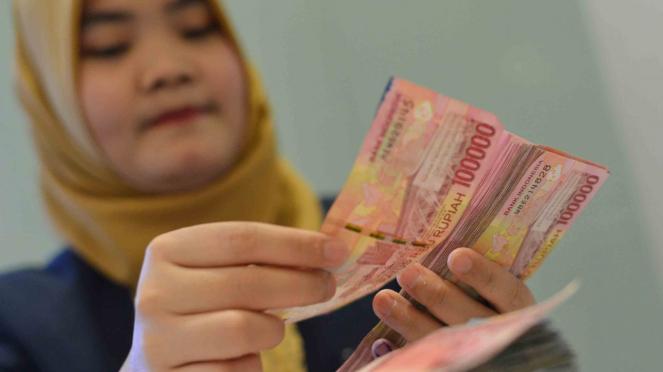 Petugas teller menghitung pecahan uang rupiah
