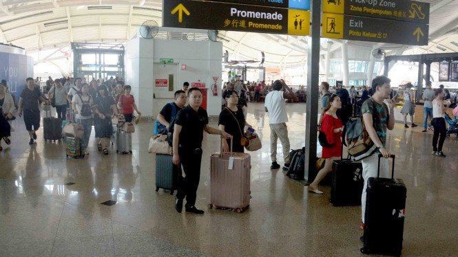 Sejumlah penumpang beristirahat menunggu jadwal penerbangan di Bandara Ngurah Rai, Bali.