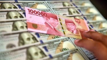 Petugas jasa penukaran valuta asing memeriksa lembaran mata uang rupiah dan dolar AS di Jakarta