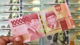 Petugas jasa penukaran valuta asing memeriksa lembaran mata uang rupiah dan dolar AS di Jakarta.