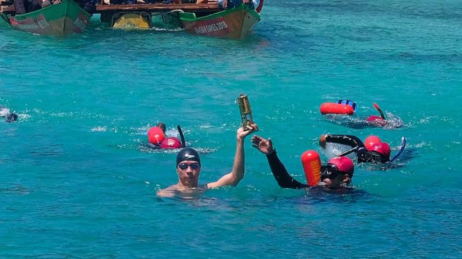 Mantan perenang Richard Sam Bera berenang sambil membawa obor Asian Games 2018 di perairan Raja Ampat, Papua Barat