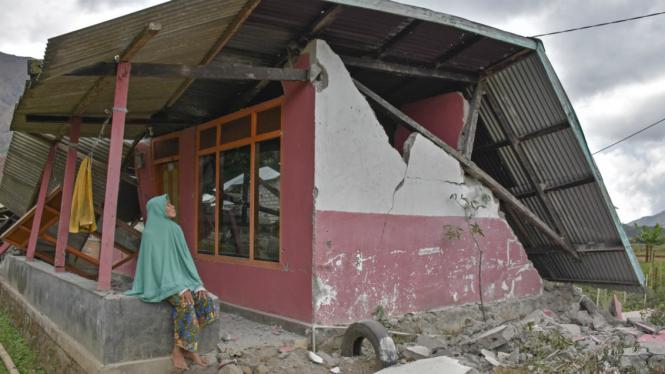Warga berada di rumahnya yang roboh akibat gempa di Desa Sembalun Bumbung, Kecamatan Sembalun, Selong, Lombok Timur, NTB, Minggu (29/7/2018).