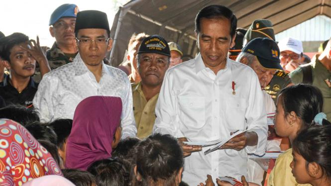 Presiden Joko Widodo (kanan) didampingi Gubernur NTB TGB Zainul Majdi (kedua kiri) membagikan buku kepada anak-anak korban gempa di Desa Madayin, Kecamatan Sambelia, Selong, Lombok Timur, NTB