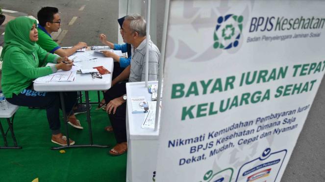 Petugas Badan Penyelenggara Jaminan Sosial (BPJS) Kesehatan memberikan informasi kepada warga