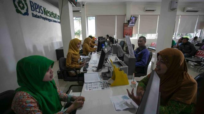 Petugas melayani warga di kantor Badan Penyelanggara Jaminan Sosial (BPJS) Kesehatan.
