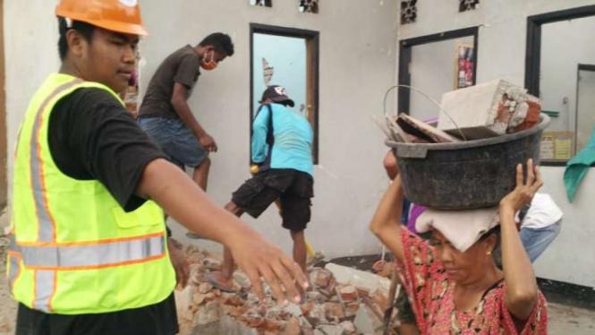 Pengungsi di Lombok Barat bersama relawan membangun kembali rumah mereka.