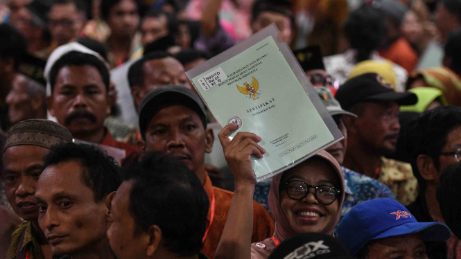Warga menunjukkan sertifikat tanah miliknya.