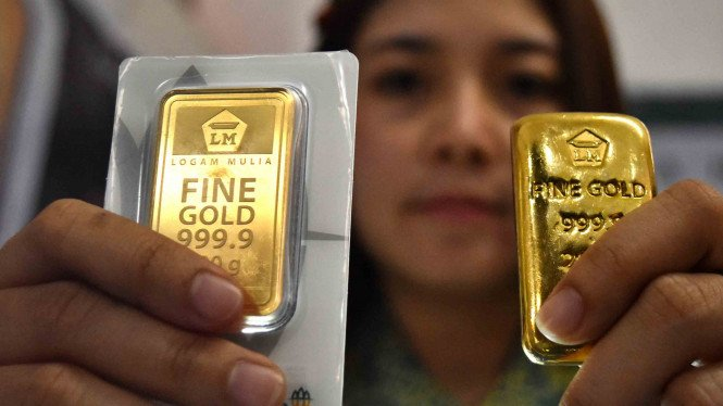 Petugas menunjukkan imitasi emas logam mulia produk PT Aneka Tambang (Antam) yang dipamerkan di gerai Antam.