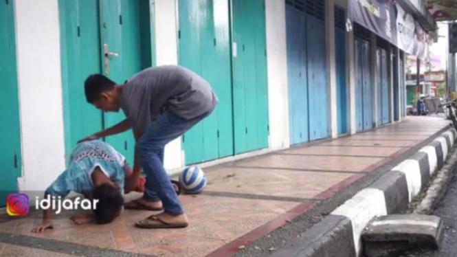 Seorang anak terjatuh usai menendang bola.